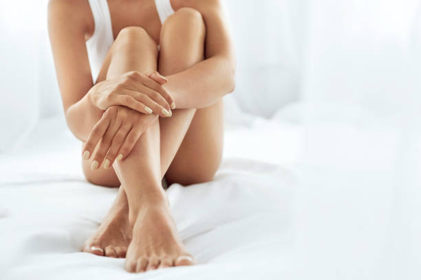 woman body care. close up of long legs with soft skin and hands - smooth stock photos and pictures