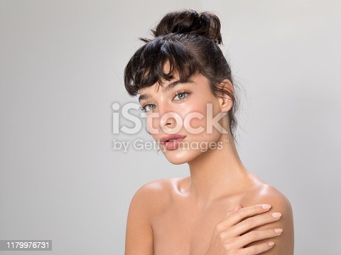Close up studio shot of a beautiful woman with perfect skin, she applying cream at her shoulder