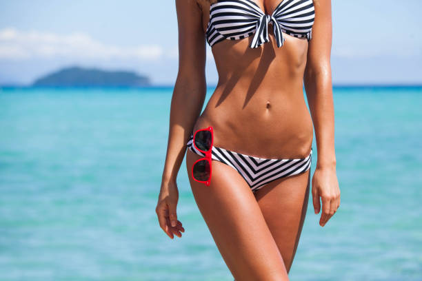 Woman body in bikini and sunglasses stock photo