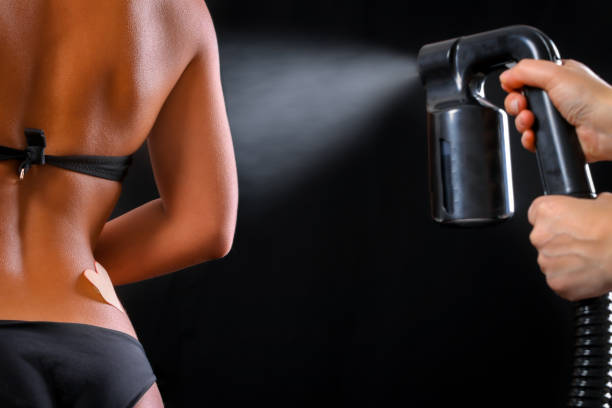 Woman body paint with airbrush in professional beauty salon Woman body paint with airbrush in professional beauty salon airbrush stock pictures, royalty-free photos & images