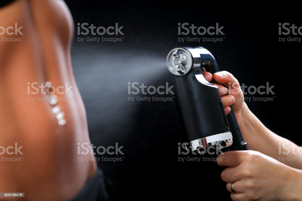Woman body paint with airbrush in professional beauty salon stock photo