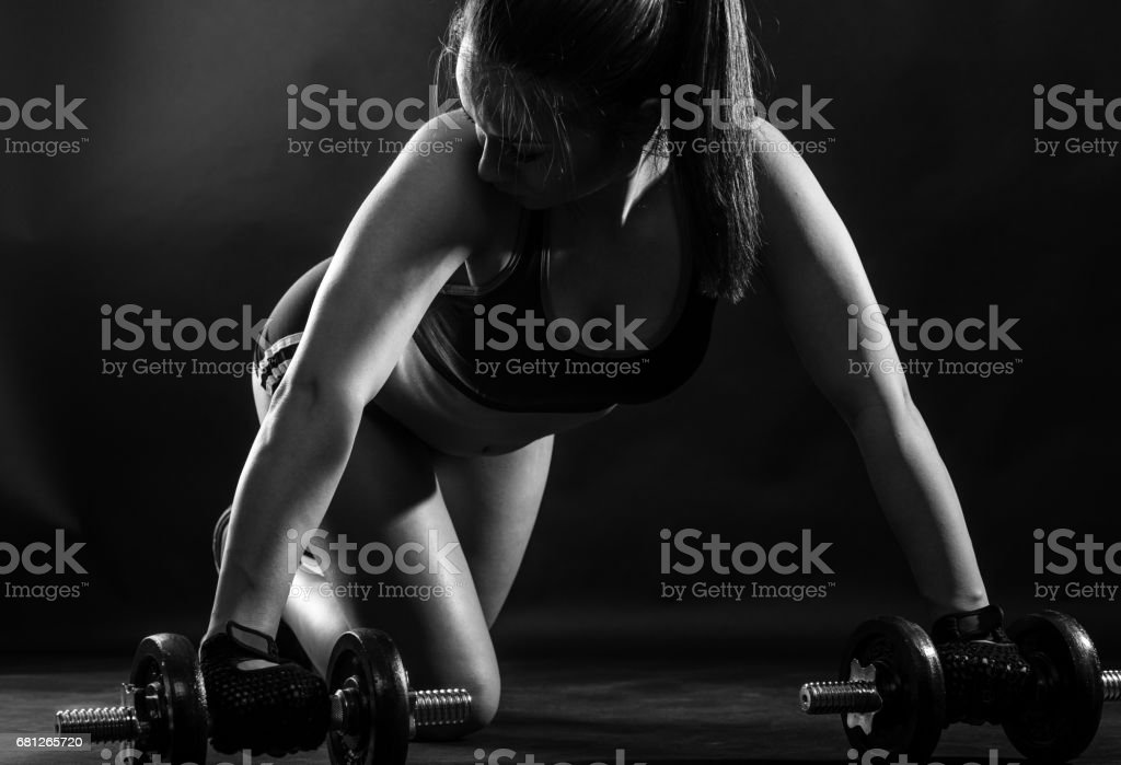 Woman bodybuilder lifting dumbbell isolated over black background, Black and white. royalty-free stock photo