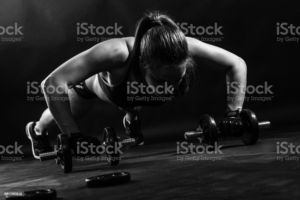 Woman bodybuilder lifting dumbbell isolated over black background, Black and white. stock photo