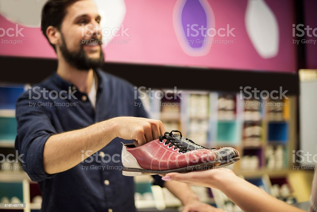 Woman borrowing a pair of bowling shoes stock photo