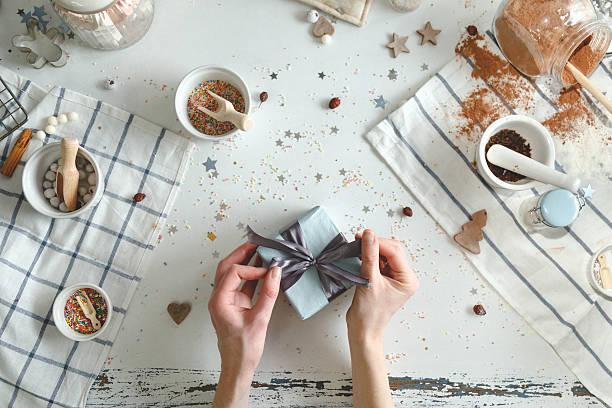 woman bows tie on christmas present with a blue ribbon - diy xmas stock-fotos und bilder