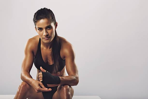 Woman boxer getting ready for workout stock photo