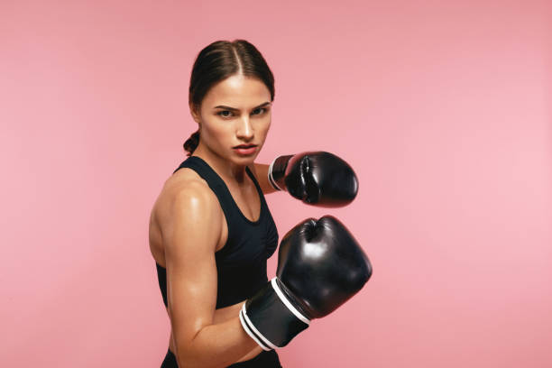 woman boxer in gloves training on pink background - combat sport stock pictures, royalty-free photos & images