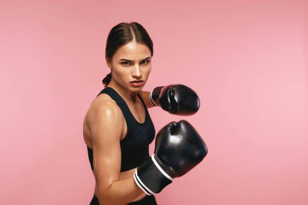 Boxer femme en gants formation sur fond rose - Photo