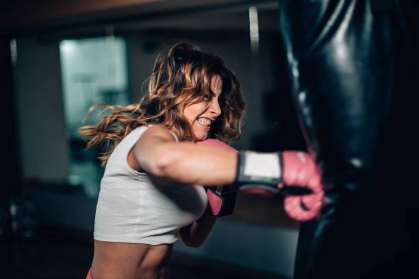 woman boxer punching a punching bag - combat sport stock pictures, royalty-free photos & images