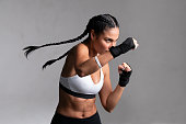 istock Woman boxer punching during training 1272778119