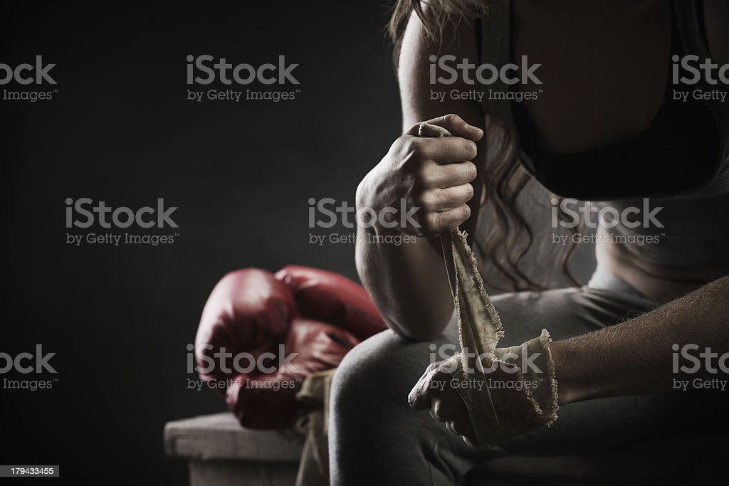 Woman boxer wrapping bandage around hand prior to game stock photo