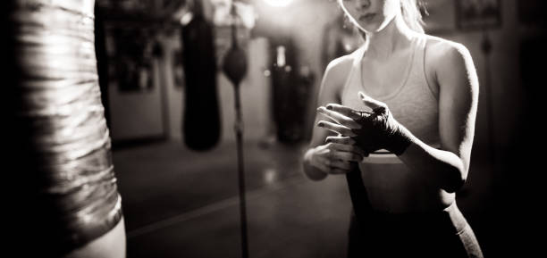 Woman boxer wrapping bandage around her hands for a fight stock photo