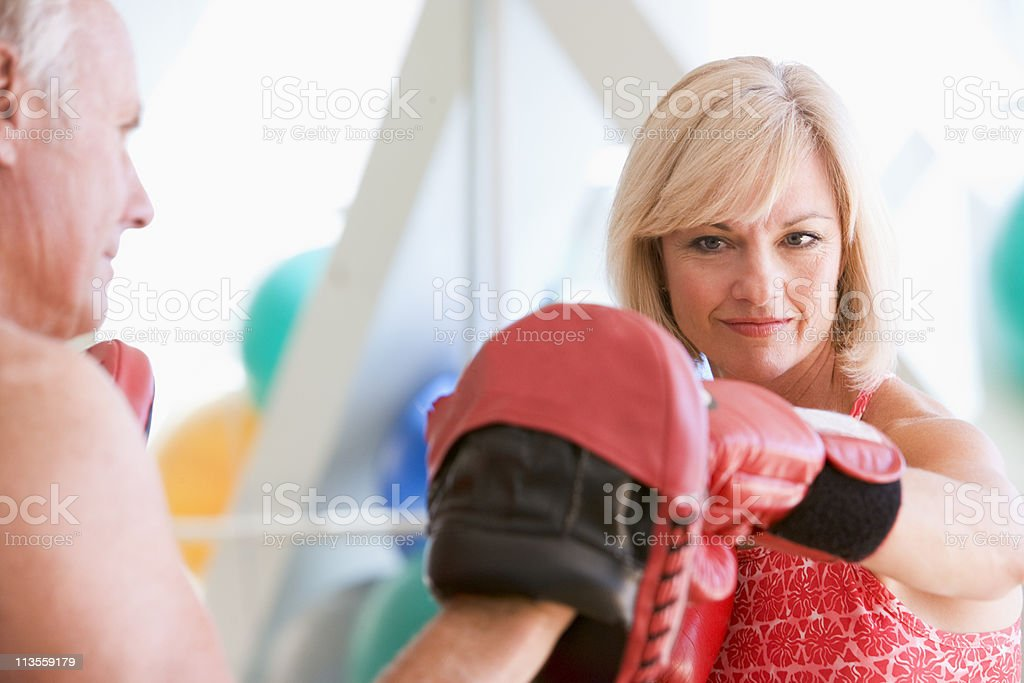 Woman Boxing With Personal Trainer At Gym stock photo