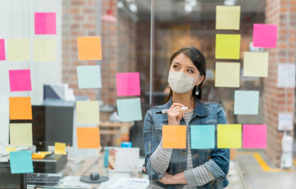 Woman brainstorming at the office while wearing a facemask stock photo
