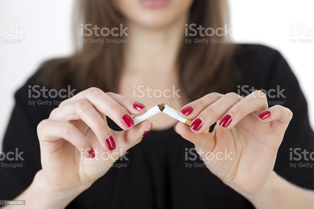 woman breaking a cigarette stock photo