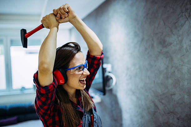 Woman breaking the wall A female handy woman working indoors,holding hammer furious stock pictures, royalty-free photos & images