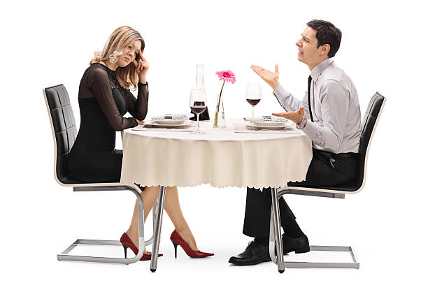 Woman breaking up with her boyfriend Young woman breaking up with her boyfriend seated at a restaurant table isolated on white background bad date stock pictures, royalty-free photos & images