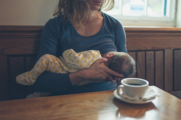 woman breastfeeding baby in cafe - femme allaite photos et images de collection