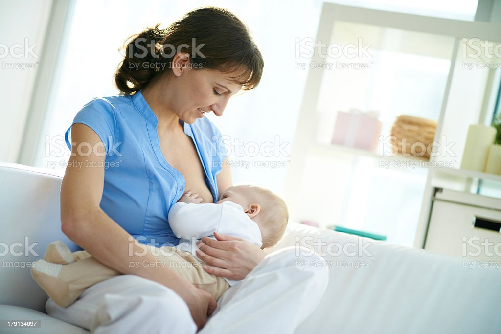 Sensational Woman Breastfeeding Baby On White Couch Stock Photo Dailytribune Chair Design For Home Dailytribuneorg