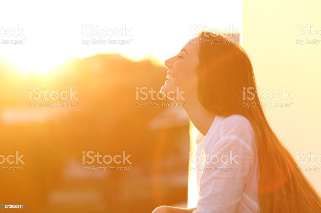 Woman breathing at sunset in a balcony stock photo