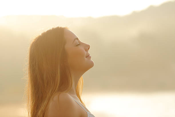 Woman breathing deep fresh air in the morning sunrise stock photo
