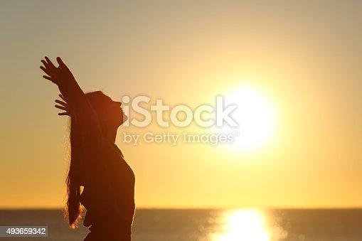 istock Woman breathing fresh air at sunset 493659342