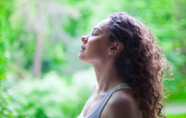 Woman breathing fresh air outdoors in summer Young woman enjoying yoga, relaxing, feeling alive, breathing fresh air, calm and dreaming with closed eyes, in public park deep stock pictures, royalty-free photos & images