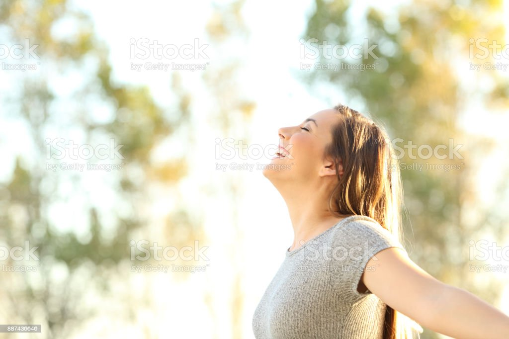 Woman breathing fresh air outdoors in summer stock photo