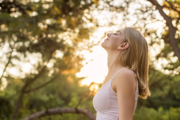 Woman breathing fresh in forest stock photo