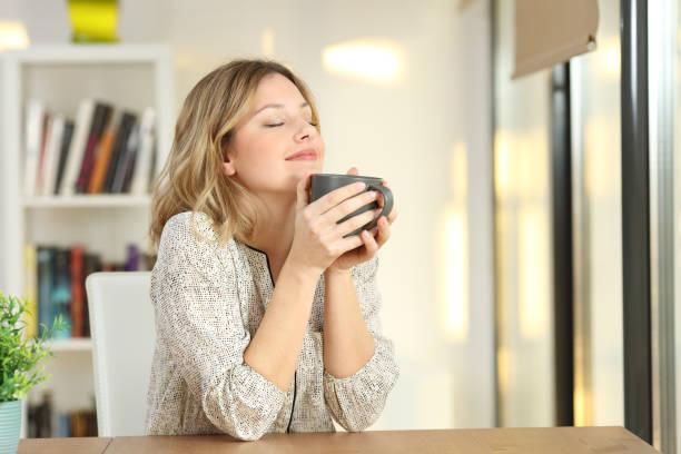 mujer sosteniendo una taza de café en casa de respiración - café bebida fotografías e imágenes de stock