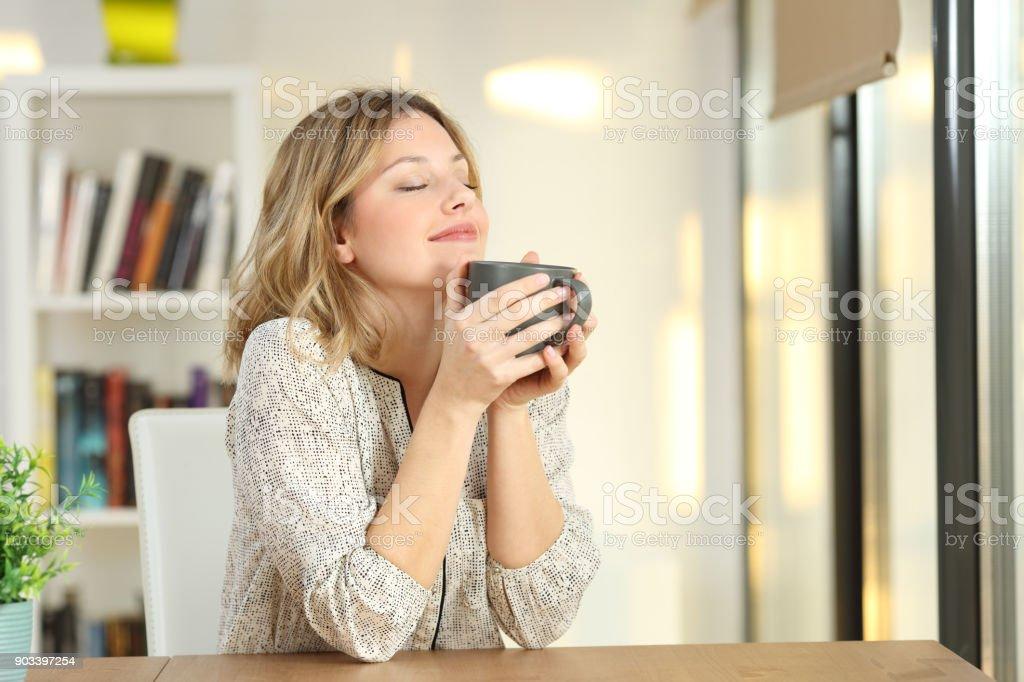 Mujer sosteniendo una taza de café en casa de respiración - foto de stock