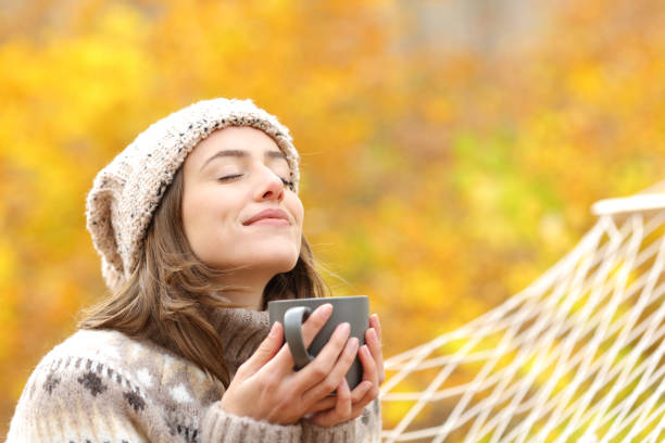 Woman breaths fresh air holding coffee cup in autumn stock photo