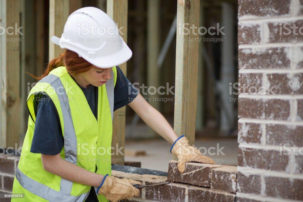 Woman bricklayer preparing laying bricks on wall stock photo