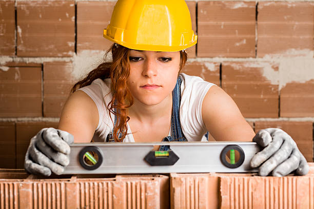 Woman Bricklayer with Spirit Level stock photo