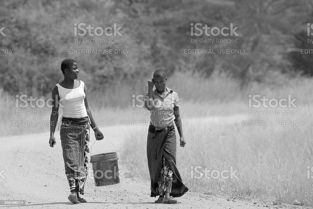 Woman bringing a bucket of water foto