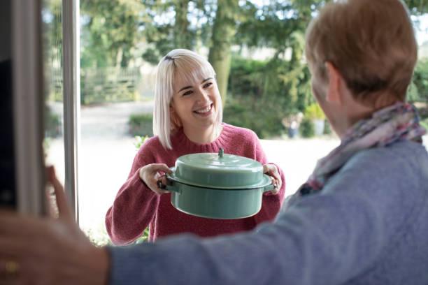 frau bringt essen für ältere nachbarin - nachbar stock-fotos und bilder
