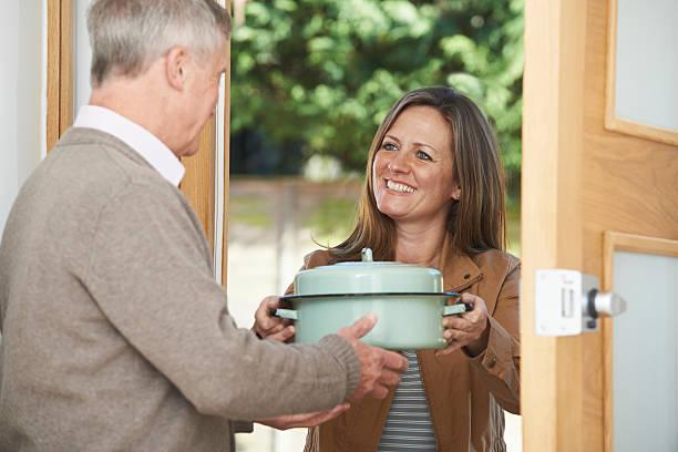 mulher trazer refeição para idosos vizinho - vizinho imagens e fotografias de stock