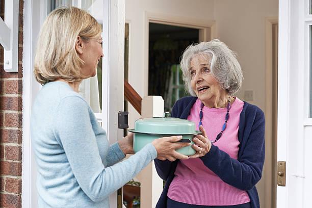 frau ihr essen für die älteren nachbarn - einen gefallen tun stock-fotos und bilder