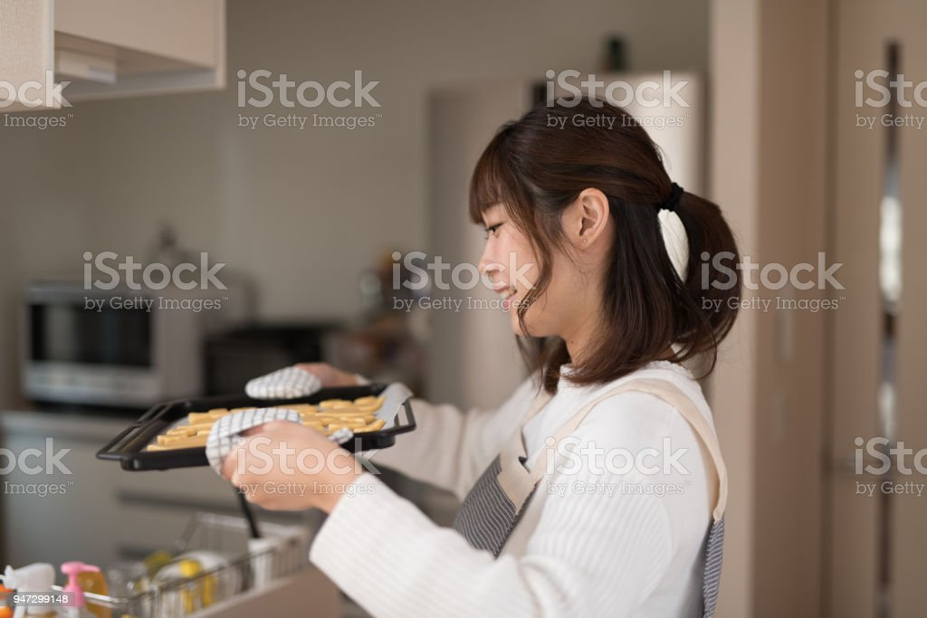 Woman bringing pastry on tray to oven stock photo