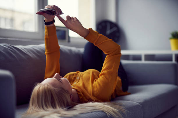 Woman browsing internet on her smartphone lying on the sofa at home Woman browsing internet on her smartphone lying on the sofa at home effortless stock pictures, royalty-free photos & images