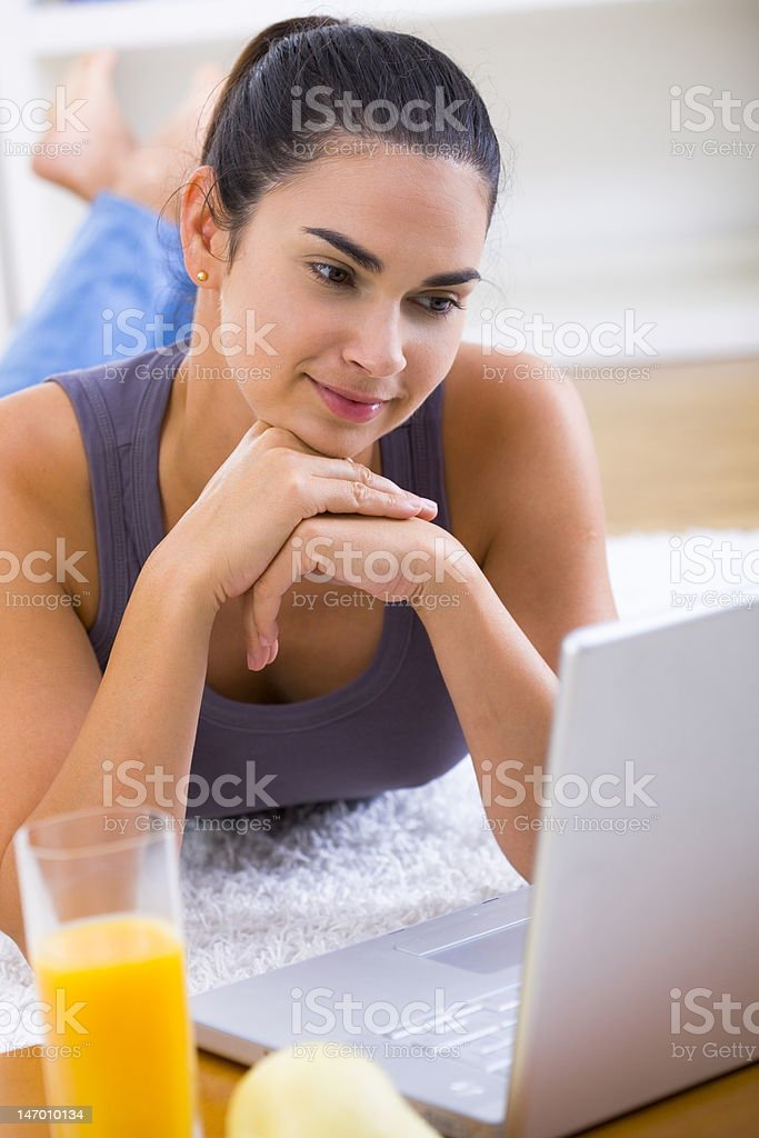 Woman browsing internet on laptop at home royalty-free stock photo