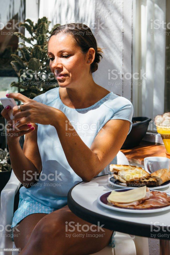 流覽手機吃早餐的女人 免版稅 stock photo
