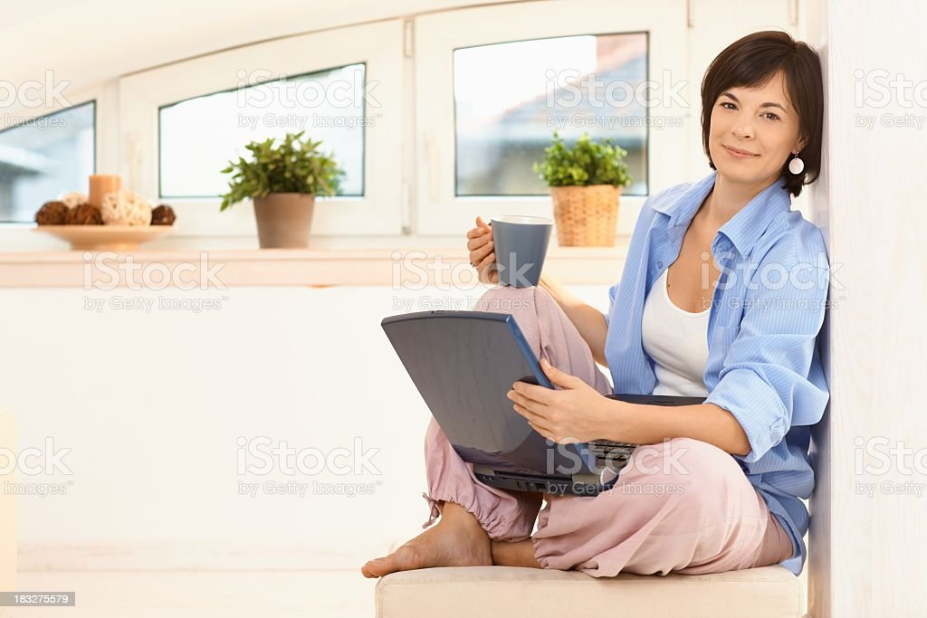 Woman browsing the internet at home on laptop computer royalty-free stock photo