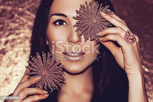 455111881 istock photo Woman brunette with Christmas decorations bronze snowflakes. Fashion gold make-up. 496381684