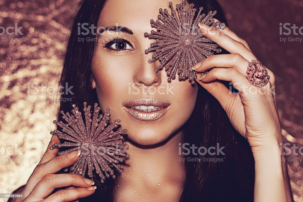 Woman brunette with Christmas decorations bronze snowflakes. Fashion gold make-up. stock photo