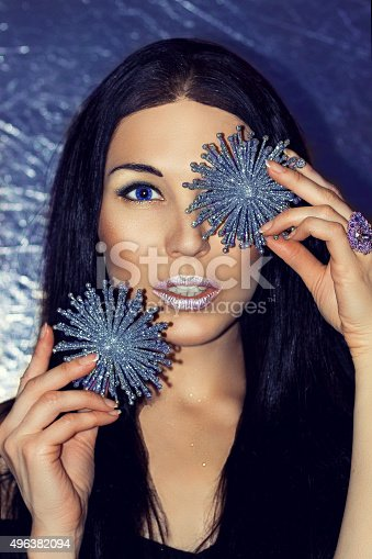455111881 istock photo Woman brunette with Christmas decorations silver snowflakes. Fashion make-up. 496382094