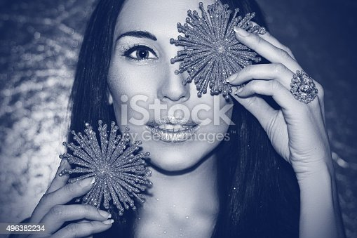 455111881 istock photo Woman brunette with Christmas decorations silver snowflakes. Fashion make-up. 496382234