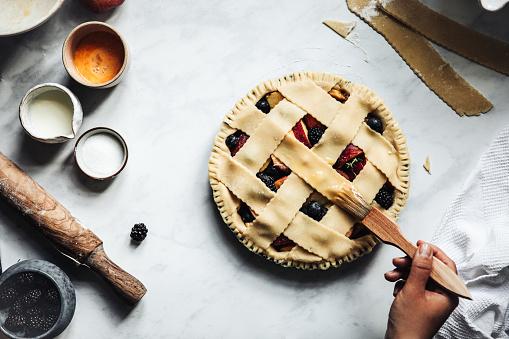 Woman working on a tasty sweet german lattice pie