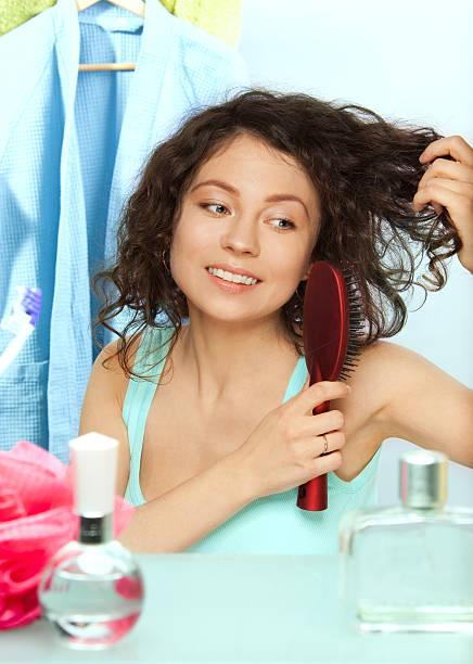 woman brushing hair in bathroom stock photo