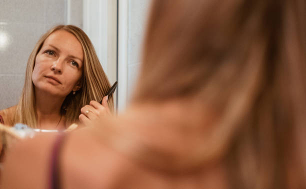 Woman brushing hair in front of mirror stock photo
